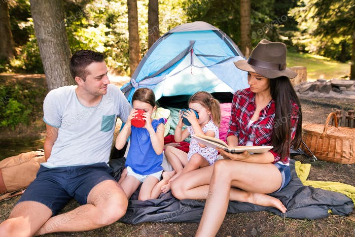 Beautiful young family with daughters camping in forest.