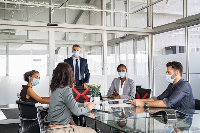 Business people wearing mask and keeping social distancing during meeting