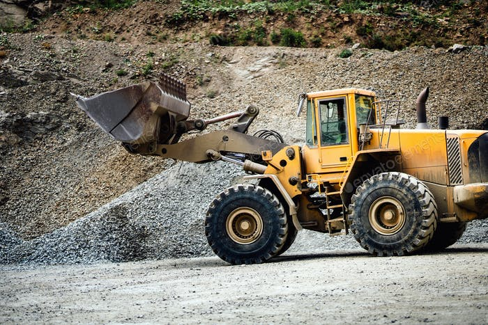 Close up details of wheel loader with scoop working on construction site