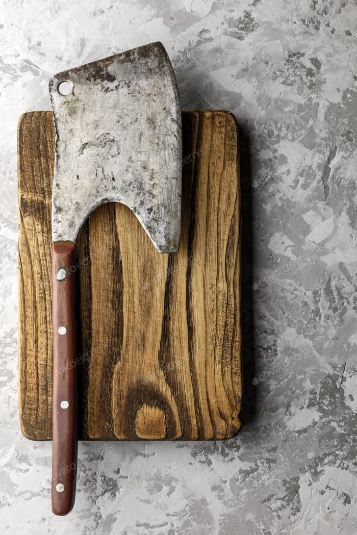 Old rustic axe for meat on a wooden board