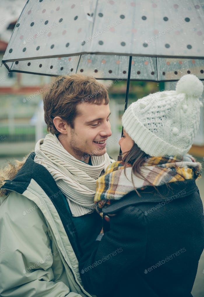 Pareja joven abrazando al aire libre bajo el paraguas en un día lluvioso