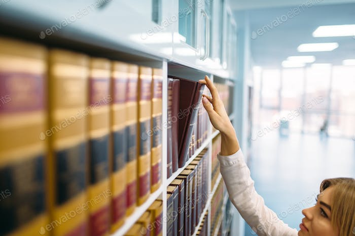 Female student looking book at the shelf, library