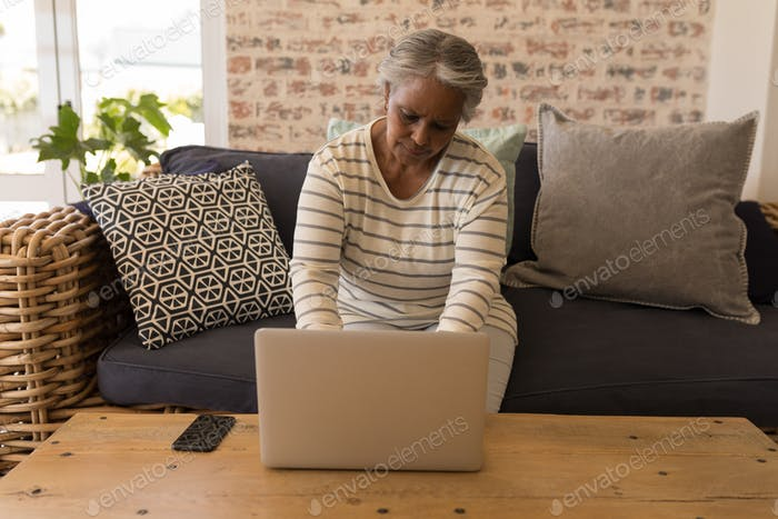 Senior woman using laptop and sitting on a sofa in living room at home