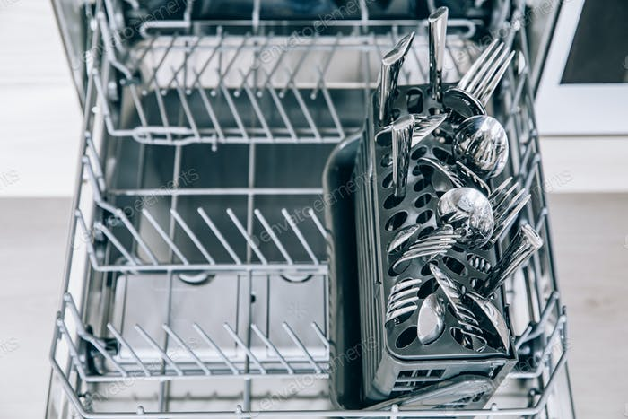 Open dishwasher machine with clean utensil close-up