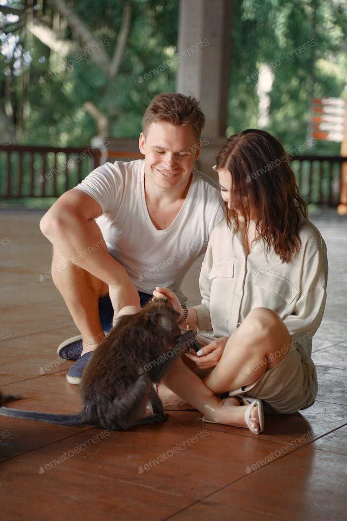 People on vacation playing with a monkey