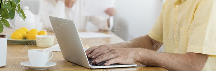 Close-up of an older man sitting by a dining table with a cup of