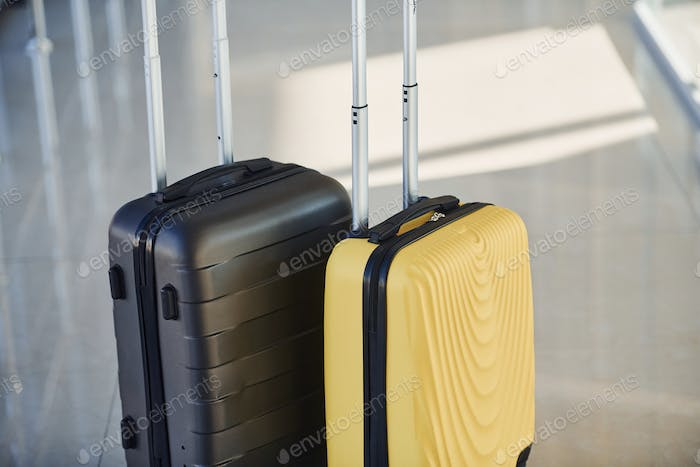 Black and white suitcases in airport hall at daytime