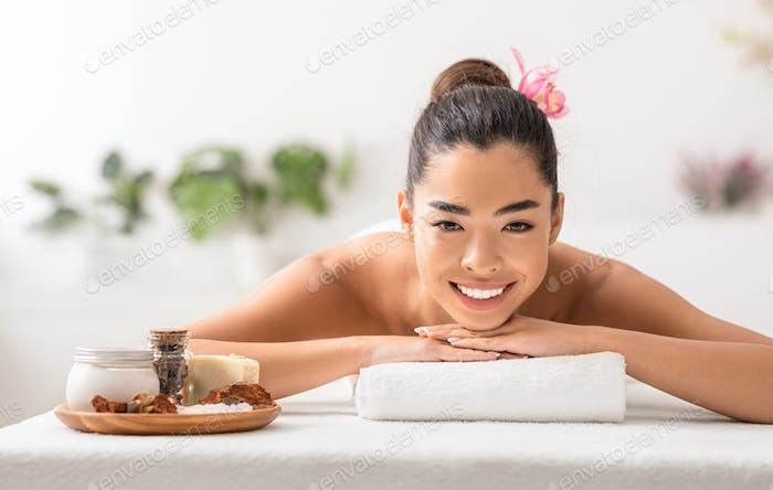 Красивая азиатская леди наслаждается косметическими процедурами с натуральной косметикой в спа-центре