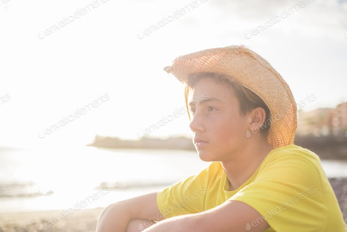 young beautiful boy 15 years old sitting on the beach in vacation looking at the horizon