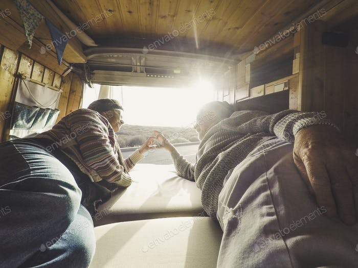 Hipster traveler adult couple enjoying the tiny van camper house lay down on the bed