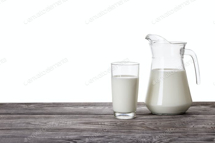 Jug and a glass of milk on a wooden table