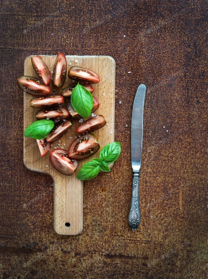 Ripe kumato tomatoes, basil leaves and knife