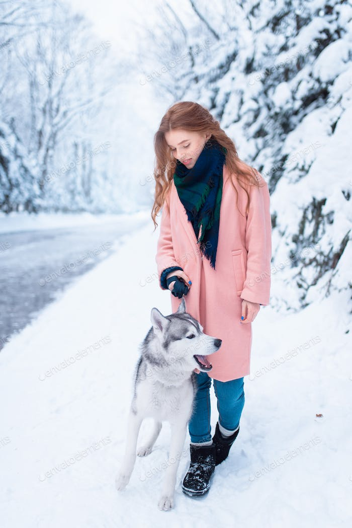 Young woman walks in the park with siberian husky