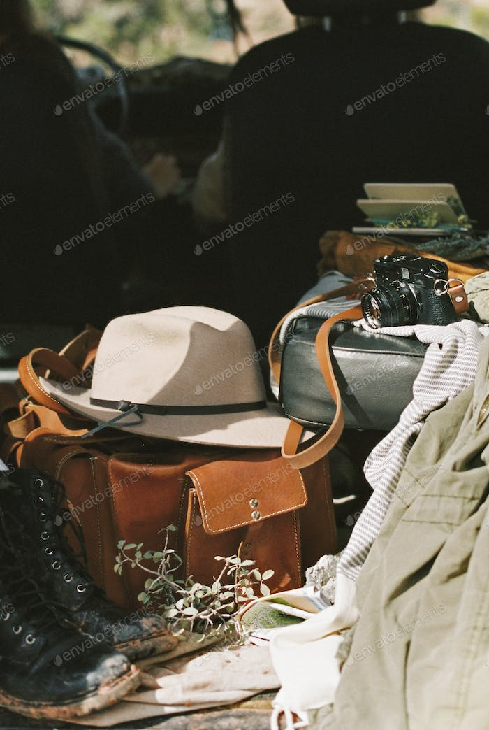 Outdoor gear including clothing, a hat, bag, camera and boots in the back of a 4x4.