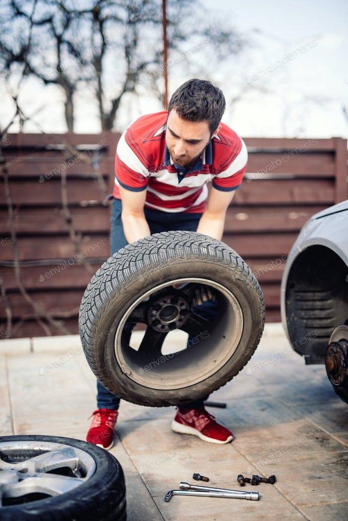 Man chaning wheel on the side of the road, flat tire details
