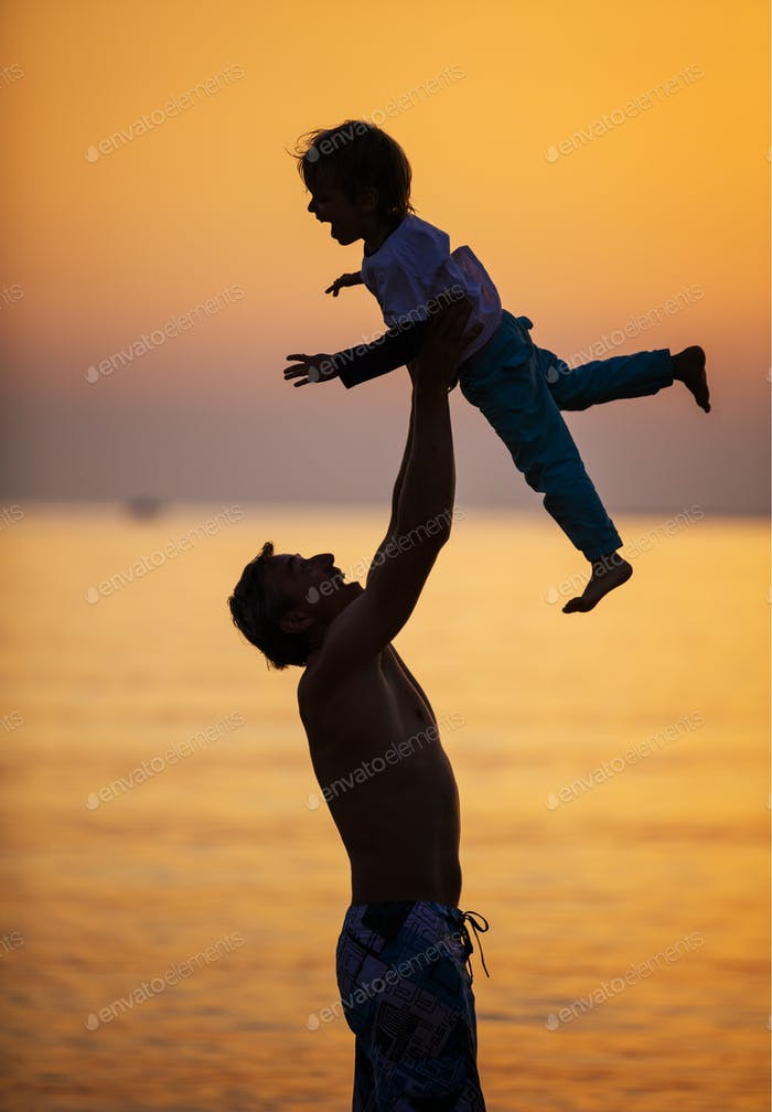 Father and son having fun on beach at sunset