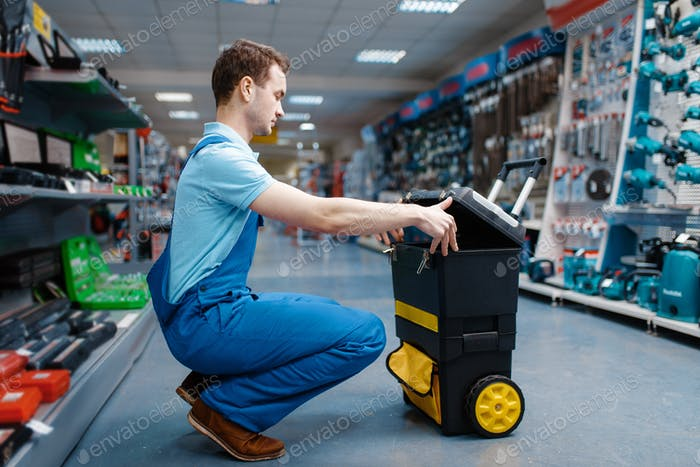 Male worker holds toolbox on wheels in tool store