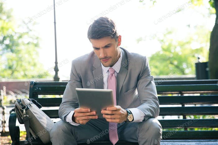 Businessman using tablet computer outdoors