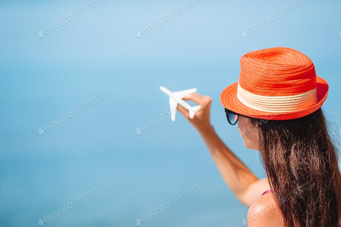 Miniature toy airplane in female hands. Trip by airplane. Conceptual image for travel and tourism
