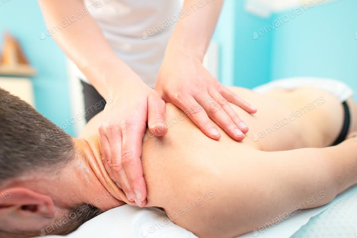 Sports back and neck treatment for a sporty man in a physiothera