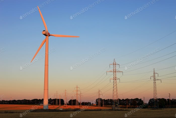 Wind turbine and electricity pylons against sky at sunset