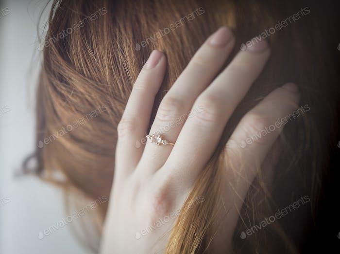 Frau läuft Finger durch Ihr Haar mit Ring