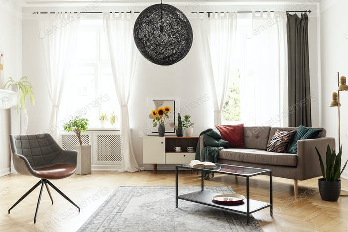 Round chandelier in a retro living room interior with a sofa, ta