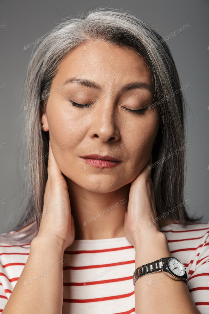 Image of adult mature tired woman wearing striped shirt touching her neck