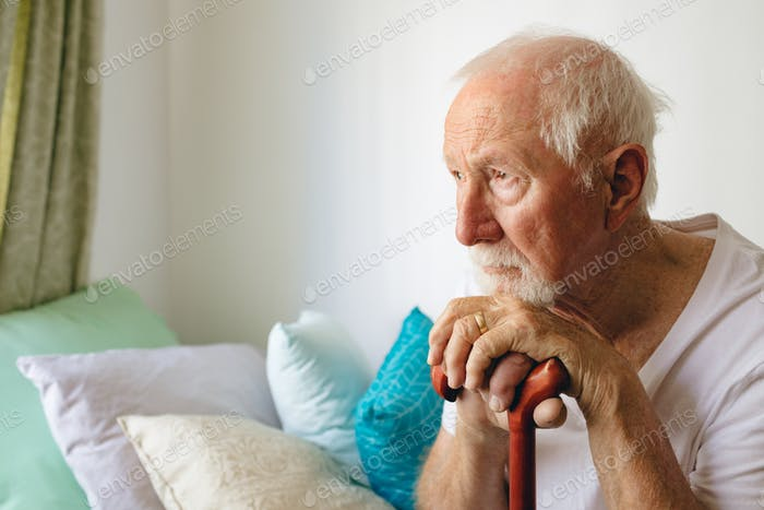 Side view of senior Caucasian male patient sitting upset on bed with stick at retirement home