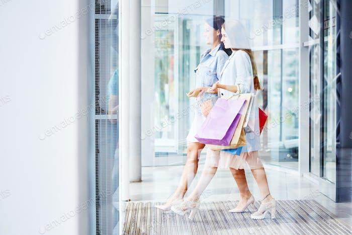 Schöne Frauen verlassen Einkaufszentrum mit Taschen