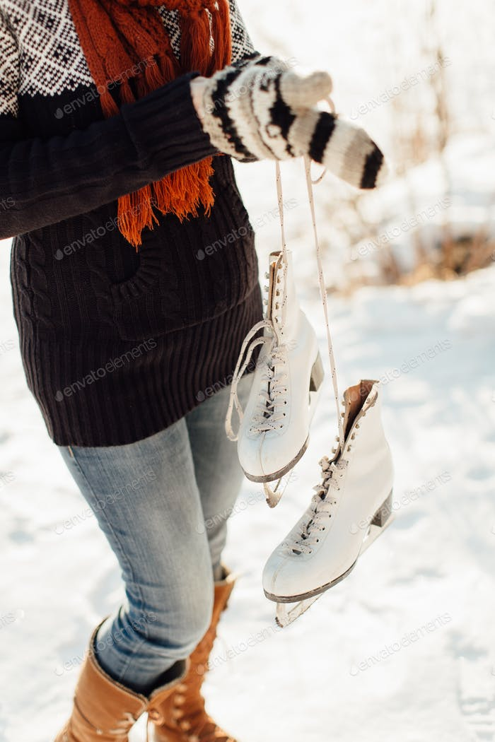Cropped image of a woman with a pair of ice skates tied together