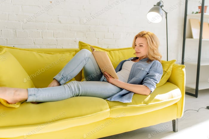 Woman lying on cozy yellow couch and reading book