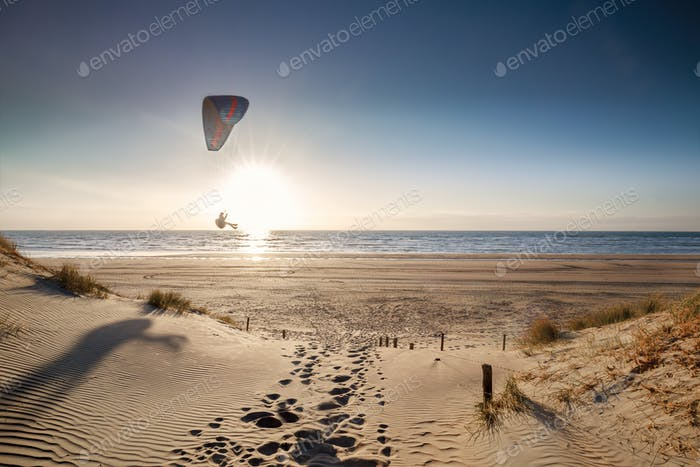 man paragliding on beach at sunset