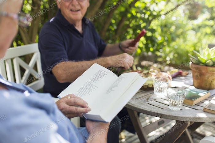 Senior woman reading book on patio