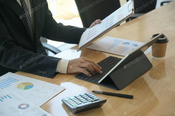 Young executives are checking company earnings. He uses tablet and check the data from chart.