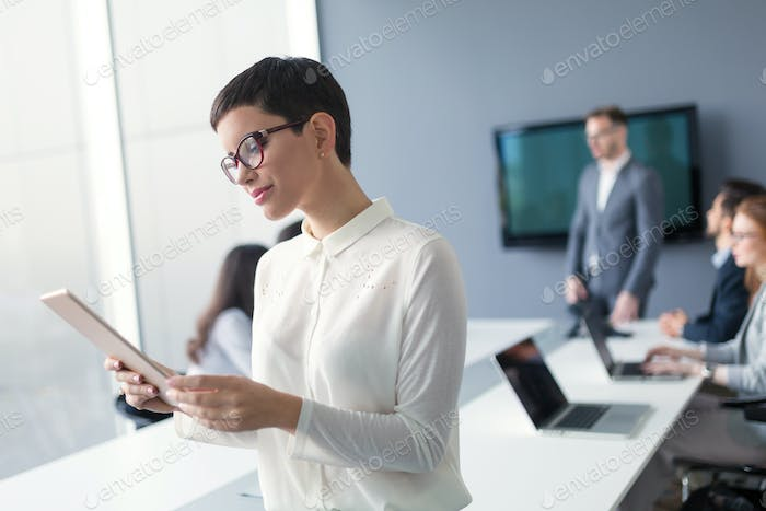 Beautiful businesswoman using tablet to gather information in of