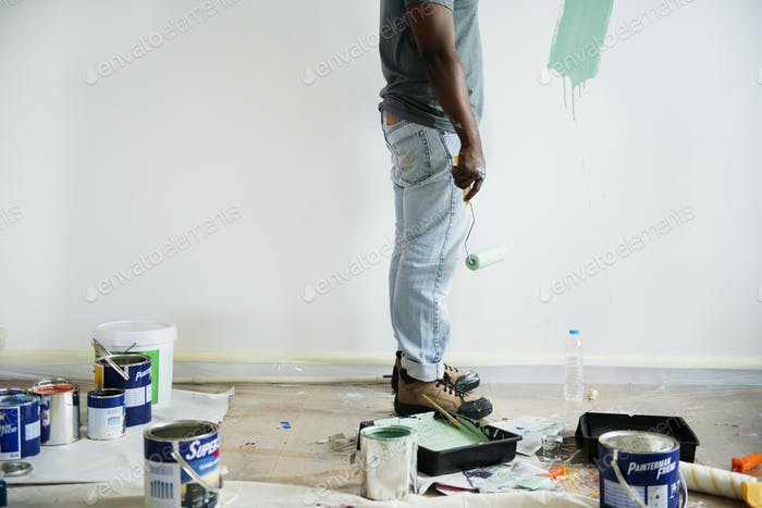 Black man painting house wall