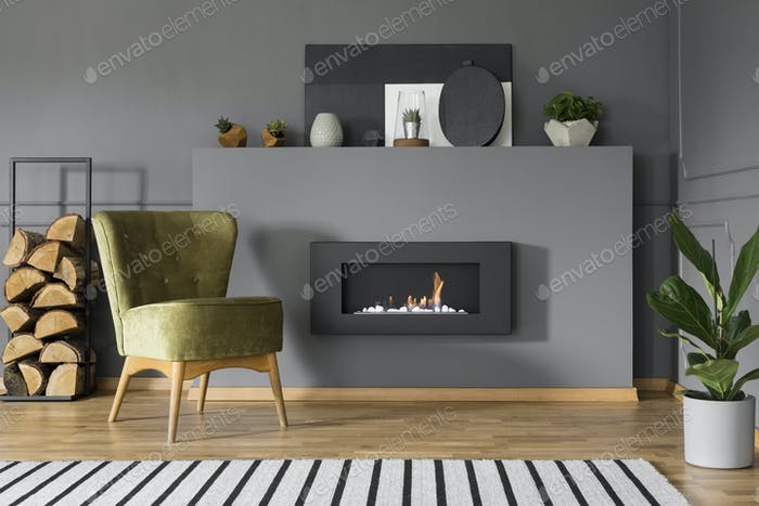 Green armchair and firewood next to fireplace in grey living roo