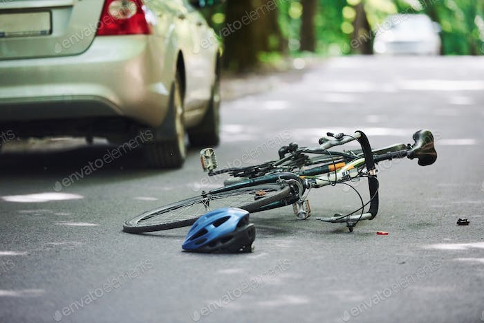 Bicycle and silver colored car accident on the road at forest at daytime