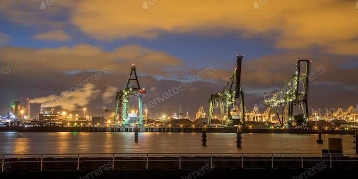 Industrial Harbor quay with loading cranes at night