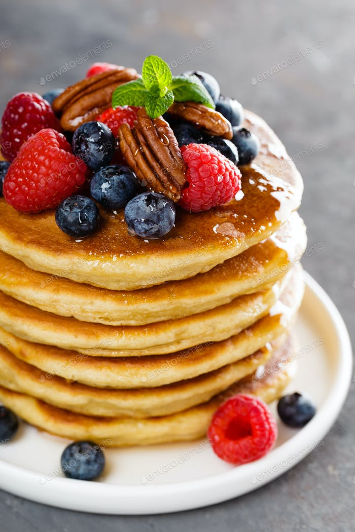 Stack of fluffy pancakes with fresh berries and pecan nuts