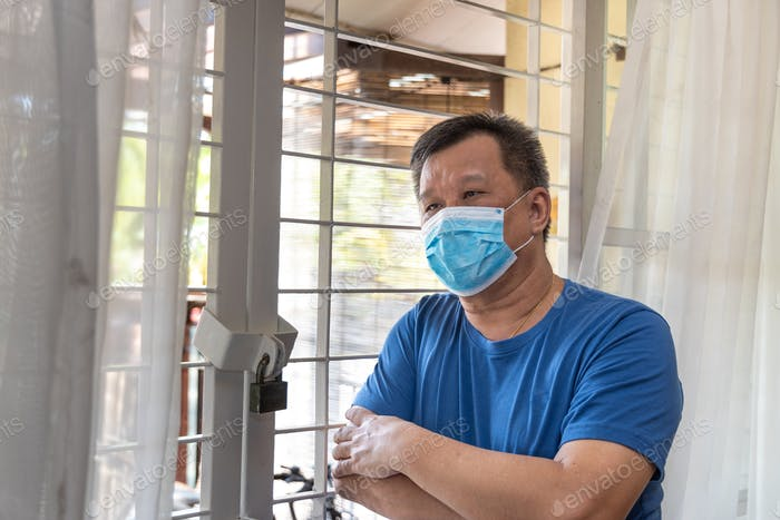 Anxious Chinese man with face mask self isolate quarantine at home for fear of covid-19 virus