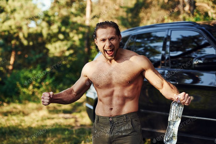 Refreshing with water. Handsome shirtless man with muscular body type is in the forest at daytime