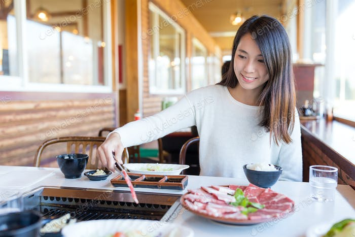 Woman having roasted sliced of beef in japanese yakiniku