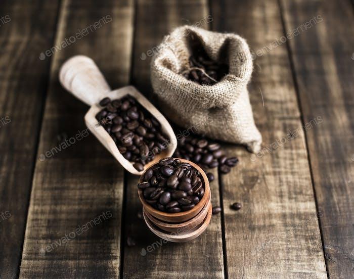 Kaffeebohnen mit Holzuntertasse Schaufel und Tasche