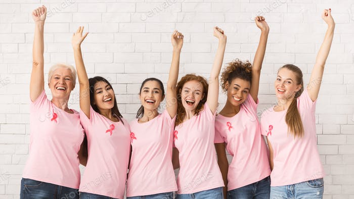 Breast Cancer Volunteers Raising Hands Supporting Awareness Campaign Indoor