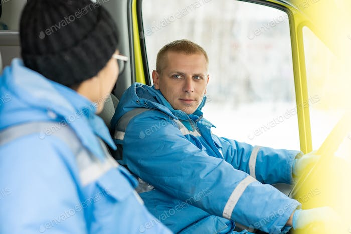 Young driver of ambulance car talking to female paramedic and steering