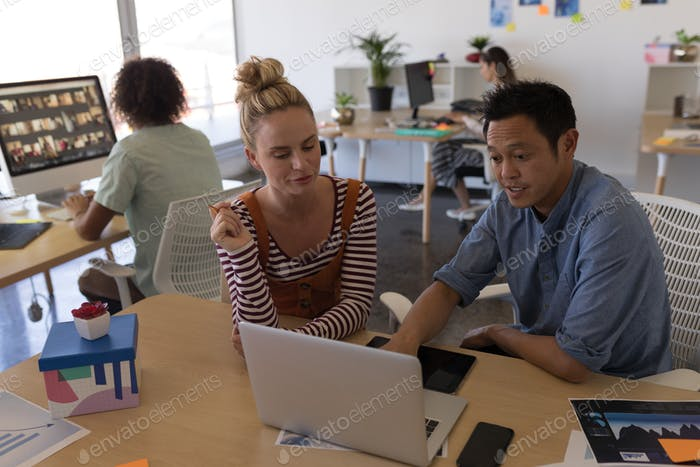 Front view of multi-ethnic business colleagues discussing business over laptop in modern office