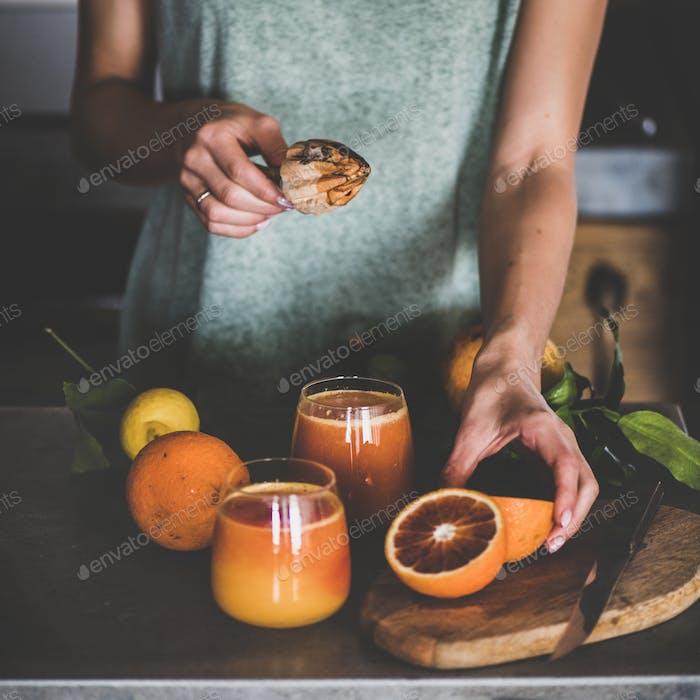 Woman making fresh blood orange juice or smoothie, square crop