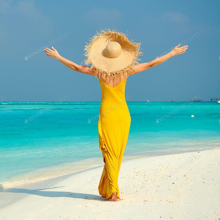 Woman in dress walking on tropical beach